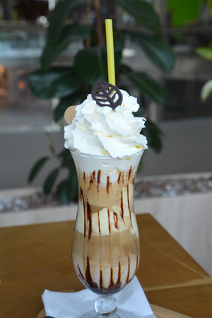 Delicious iced coffee with whipped cream on a glass cup.