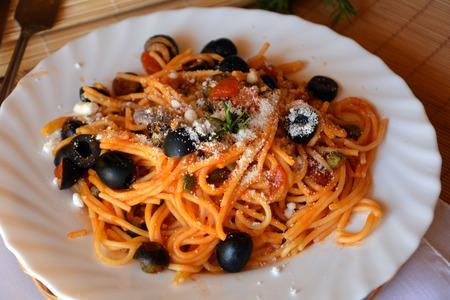 Spaghetti alla puttanesca italian pasta on a bowl on a table. Stock Photo