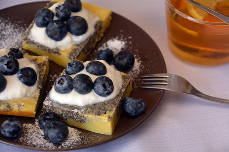 Summer dessert with ground poppy, blueberries and cottage cheese and cup of lemon tea.