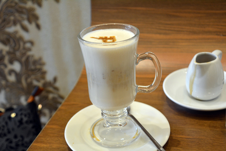Delicious foamy italian cappuccino on a cup on a wooden table.