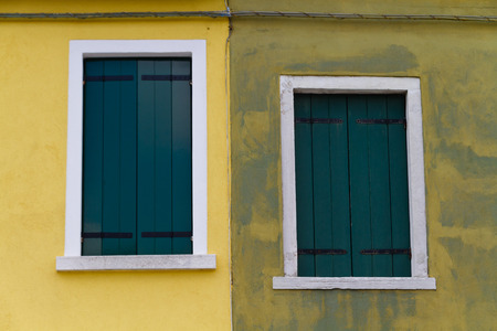 yellow wall: Closed green windows on a yellow wall