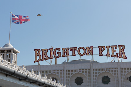 brit: Brighton Pier signage with an English flag on the roof on a sunny day with no clouds in the sky Editorial
