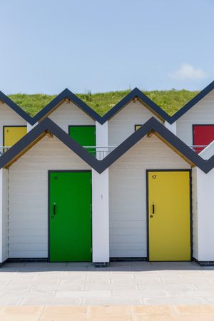 individually: Swanage England  May 2015: Colourful doors of yellow and green with each one being numbered individually of white beach houses on a sunny day