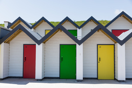 individually: Swanage England  May 2015: Colourful doors of yellow red and green  with each one being numbered individually of white beach houses on a sunny day