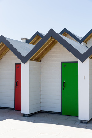 individually: Swanage England  May 2015: Colourful doors of green and red with each one being numbered individually of white beach houses on a sunny day
