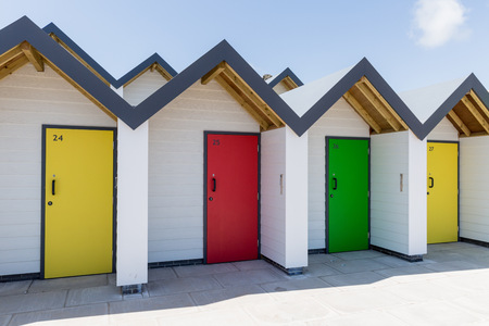 individually: Swanage England  May 2015: Colourful doors of yellow green and red with each one being numbered individually of white beach houses on a sunny day
