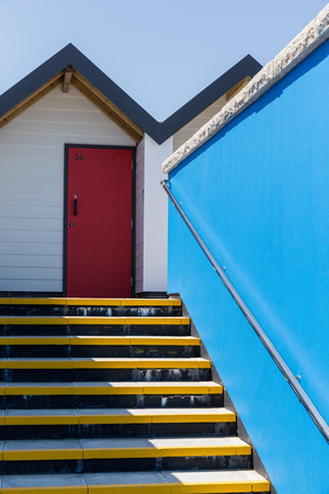 individually: Swanage England  May 2015: Colourful red door with each one being numbered individually of white beach houses on a sunny day a view looking up the yellow stairs and a blue side wall Editorial
