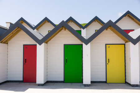 individually: Colourful doors of yellow red and green  with each one being numbered individually of white beach houses on a sunny day Editorial