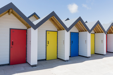 individually: Colourful doors of blue yellow and red with each one being numbered individually of white beach houses on a sunny day Editorial
