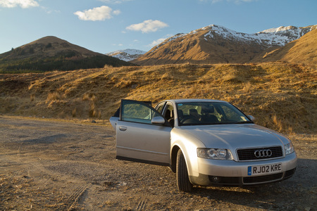 long weekend: Fort William Scotland  March 2013: A view of a grey Audi car in front of scenic scottish mountains on a sunny day with limited clouds Editorial