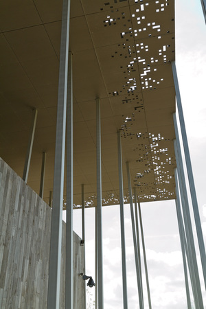 Amesbury England  circa May 2014: A detailed view of  the perforated metal roof  and the wooden structure of the Stonehenge Pavilion on a sunny day with limited clouds