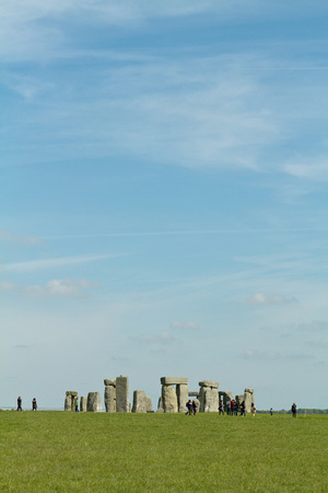 Amesbury England  circa May 2014: A view towards the Stonehenge with people walking around taken from the side of the road on a sunny day with limited clouds