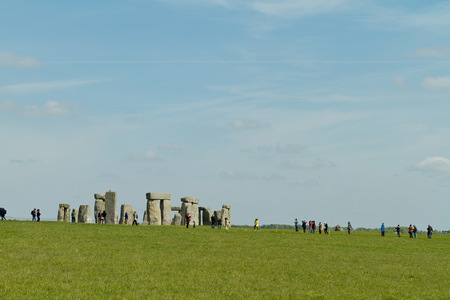 Amesbury, England - circa May 2014: A view towards the Stonehenge with people walking around taken from the side of the road on a sunny day with limited clouds
