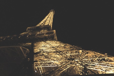 tour eiffel: Paris France  circa September 2012: A night photograph of the Tour Eiffel taking underneath the structure looking up photos has an applied Vintage filter