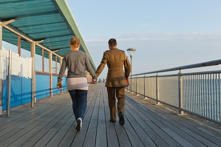 walking away: A girl in a track suit and a guy in his army suit walking away from the camera walking at the pier at sunset hour on a summer day with no clouds in the sky