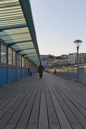 walking away: A guy in his army suit walking away from the camera walking at the pier at sunset hour on a summer day with no clouds in the sky