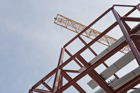 steel framing a construction site with steel framing and a yellow construction crane