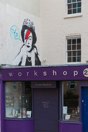 closing time: April 2014 - Bristol, United Kingdom: A graffiti of the Royal Queen with red and blue  lightning shaped make to the right closed eye. Colston Street, BH2 8DJ, Banksy art, Royal Queen