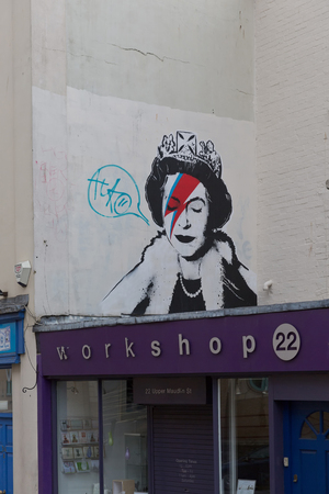 blue lightning: April 2014 - Bristol, United Kingdom: A graffiti of the Royal Queen with red and blue  lightning shaped make to the right closed eye. Colston Street, BH2 8DJ, Banksy art, Royal Queen