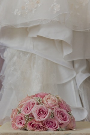 fake diamond: A coloured macro photo of a detailed bouquet with pink roses, white small flowers and a fake diamond in the centre of the roses, the wedding dress is in the back of the picture