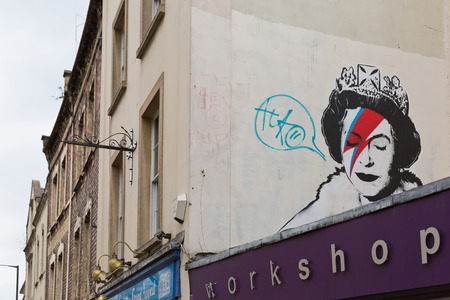 timeless: April 2014 - Bristol, United Kingdom: A graffiti of the Royal Queen with red and blue  lightning shaped make to the right closed eye. Colston Street, BH2 8DJ, Banksy art, Royal Queen