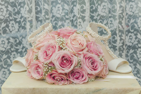fake diamond: A coloured macro photo of a detailed bouquet with pink roses, white small flowers and a fake diamond in the centre of the roses and the wedding shoes