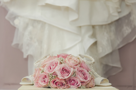 fake diamond: A coloured macro photo of a detailed bouquet with pink roses, white small flowers and a fake diamond in the centre of the roses, the wedding dress and shoes Stock Photo