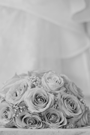 fake diamond: A black and white macro photo of a detailed bouquet with pink roses, white small flowers and a fake diamond in the centre of the roses, the wedding dress is in the back of the picture