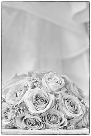 fake diamond: A coloured macro photo of a detailed bouquet with pink roses, white small flowers and a fake diamond in the centre of the roses, the wedding dress is in the back of the picture, with a vintage black border