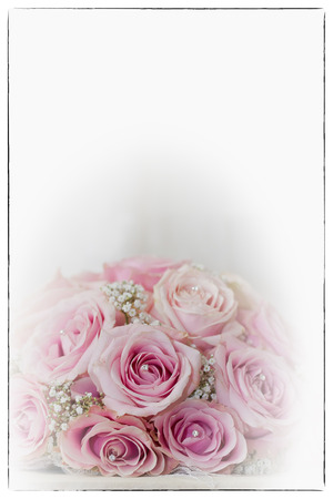 fake diamond: A coloured macro photo of a detailed bouquet with pink roses, white small flowers and a fake diamond in the centre of the roses, the wedding dress is in the back of the picture applied with a soft focus vignet blur and vintage black border