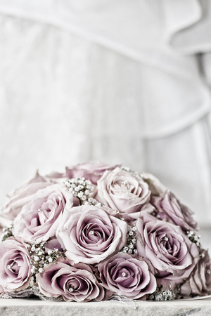 fake diamond: A coloured macro photo of a detailed bouquet with pink roses, white small flowers and a fake diamond in the centre of the roses, the wedding dress is in the back of the picture applied with a saturated vintage filter