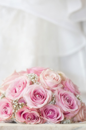fake diamond: A coloured macro photo of a detailed bouquet with pink roses, white small flowers and a fake diamond in the centre of the roses, the wedding dress is in the back of the picture applied with a soft focus blur