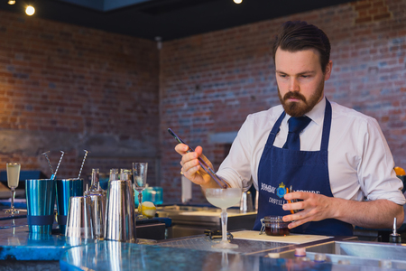 finishing touches: Laverstoke Mill, England - May 2015: Photo captured in the bar of Bombay Sapphire Distillery looking at the bartender making cocktails using a tweezer for finishing touches