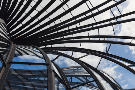 intertwined: A coloured photograph of intertwined curved lines of aluminium structures with glass in between them