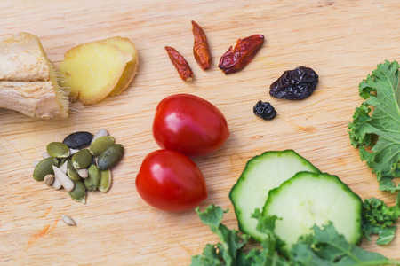 heart chakra: Ingredients of a healthy green juice smoothie: fresh ginger, avocado, tomatoes, kale and garnished with pumkin seeds, sunflower seeds, flax seeds Stock Photo