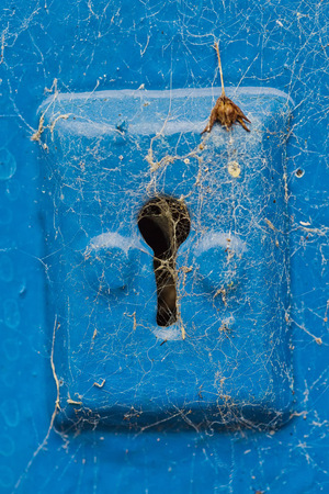 key hole: Cobwebs on a blue metail key hole of a blue wooden door Stock Photo