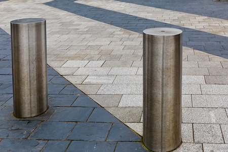 Stainless Steel bollard on grey pavement with a few lines of dark grey paving slabs Stock Photo