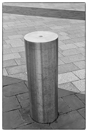 Black and white photo of a Stainless Steel bollard on grey pavement with a few lines of dark grey paving slabs with a vintage border