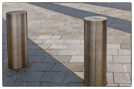 Stainless Steel bollard on grey pavement with a few lines of dark grey paving slabs with a vintage border