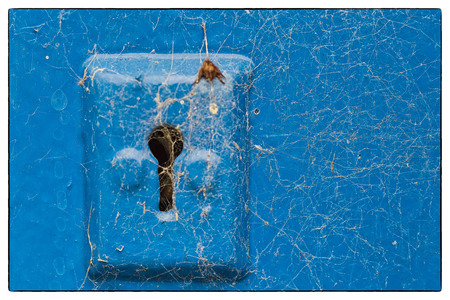 peephole: Cobwebs on a blue metail key hole of a blue wooden door. Vintage border Stock Photo
