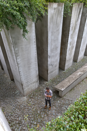 exile: July 2015 - The Jewish Museum Berlin, Berlin, Germany: The Garden of Exile and Emigration.The 49th column, filled with earth from Jerusalem, stands for Berlin. Man reading and standing still Editorial