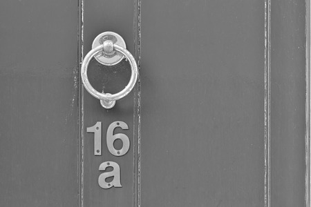mail slot: English period wooden front door with ornate iron door knocker. House number position under door knocker. Black and white photo