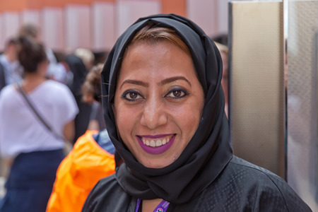 life partners: MILAN, ITALY - September 2015: Beautiful smiling woman working for United Arab Emirates pavilion pavilion at World Expo, universal exposition on the theme of Feeding the Planet Energy for Life. Pavilion designed by Fosters and Partners Editorial