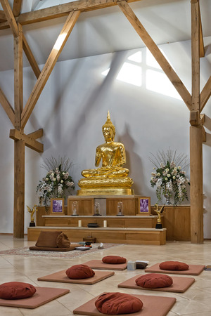 dhamma: Hemel Hempstead, England - November 2016: Inside the Temple of Amaravati Buddhist Monastery. The monastery is inspired by the Thai Forest Tradition and the teachings of the late Ajahn Chah, a Thai monk, a Thai monk and renowned Dhamma teacher. Editorial