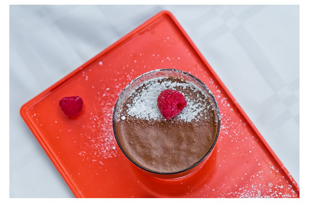 Homemade chocolate mousse with fresh raspberries on an orange serving plate, top view. Stock Photo