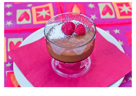 Homemade chocolate mousse with fresh raspberries on a red napkin Stock Photo