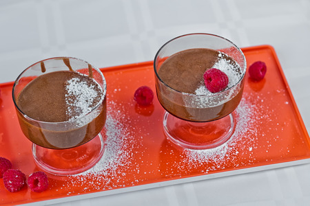 Homemade chocolate mousse with fresh raspberries on a table, top view.