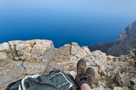 Woman with hiking boots sitting on rocks eating a snack while admiring a beautiful seascape view of the sea and rocky shore, the Aegean Sea, Amorgos Island, Greece Stock Photo