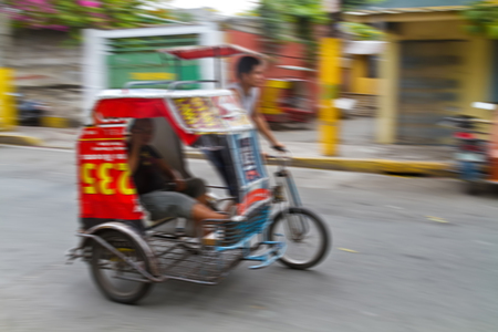 panning shot: Panning photograph of unidentified man riding Tricycle Taxi. They are often seen in city area, where public transportation services are insufficient and most residents cant afford high commuting costs, Philippines