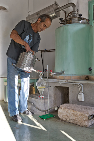 Amorgos Island, Greece - October 2015: A man during the traditional distillation process and production of homemade essential oil